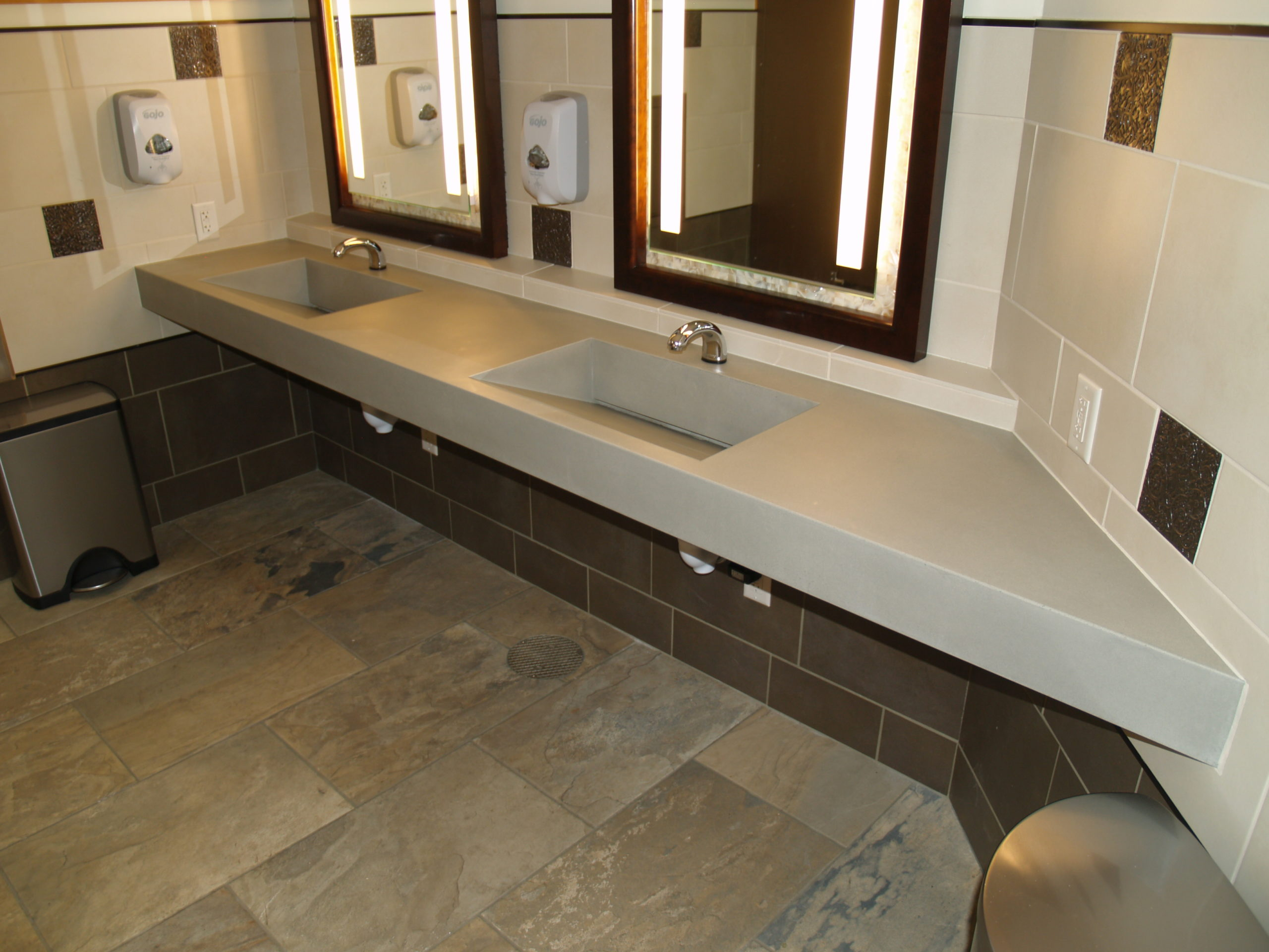 2 concrete sinks in a bathroom